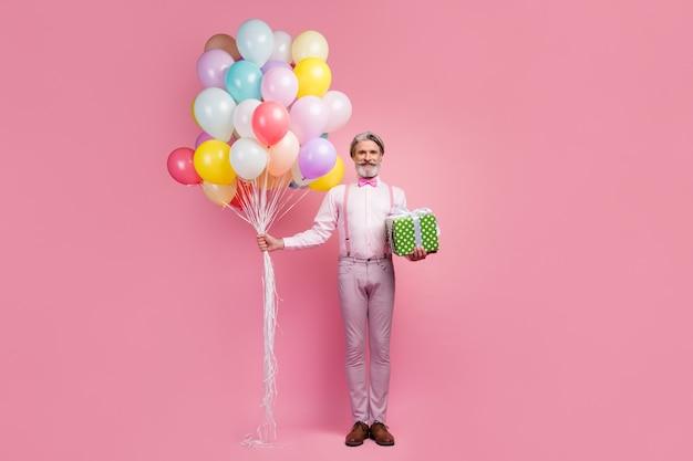Вид в полный рост седого мужчины, держащего в руках подарочную коробку с воздушными шарами