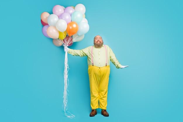 Вид в полный рост парня, держащего в руке кучу воздушных шаров