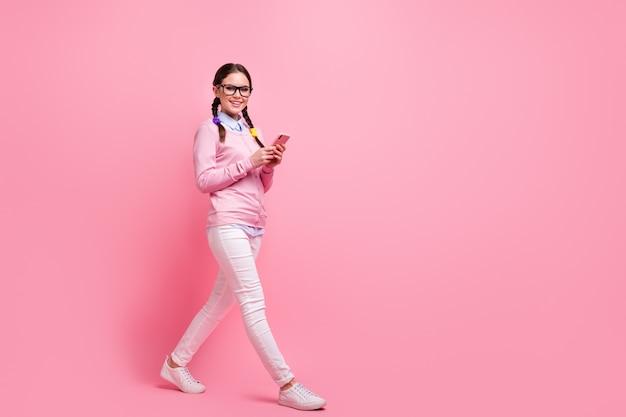 Полноразмерный вид ее тела, она привлекательная, симпатичная, довольно веселая, веселая, веселая девушка-компьютерщик, прогуливающаяся с использованием цифрового устройства приложение 5g, оставляющее комментарий, отзыв, изолированный на розовом пастельном цвете