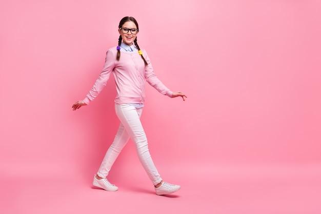 Вид ее в полный рост, она привлекательная, милая, довольно довольная, рада, веселая, веселая, шатенка, ботаник, гуляет, прогуливается, изолирована на розовом фоне пастельных тонов.