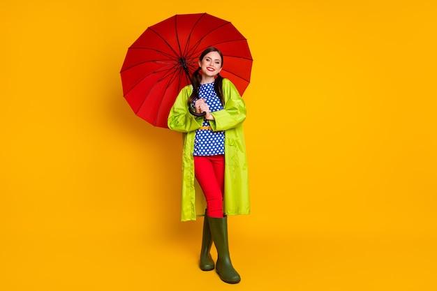 Полный размер тела вид ее она красивая привлекательная веселая веселая радостная модная девушка в зеленом плаще с открытым зонтиком изолирована ярким ярким блеском яркого желтого цвета фона