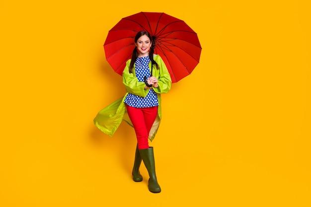 Полная длина тела вид ее она красивая привлекательная модная веселая веселая довольная девушка в зеленом пальто с открытым зонтиком прогуливается изолированно яркий яркий блеск яркий желтый цвет фона