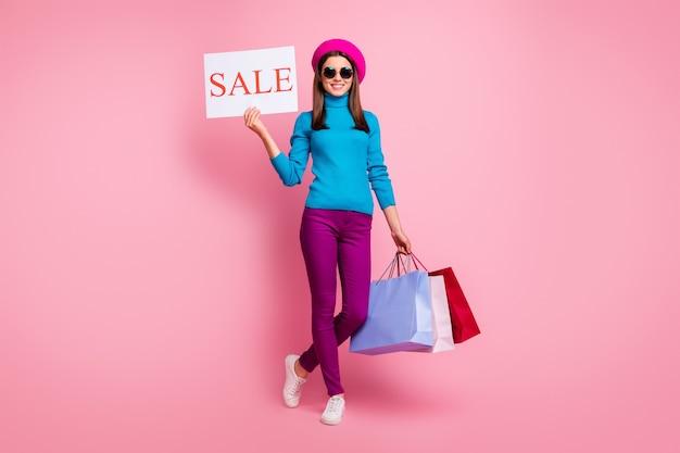 В полный рост вид ее она милая привлекательная модная жизнерадостная веселая девушка держит в руках сумки промо рекламный щит открытия магазина.