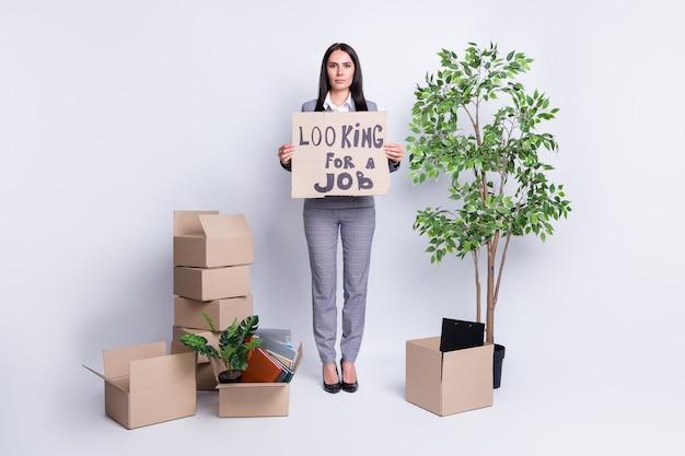 彼女の全身サイズのビュー彼女の素敵な魅力的な解雇された女性の応募者候補不動産業者は、仕事の履歴書の欠員を探していると言って紙のカードを保持している孤立した灰色のパステルカラーの背景