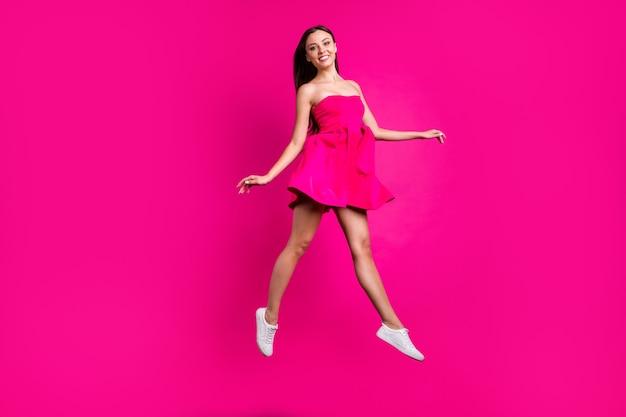 Вид ее в полный рост, она красивая, привлекательная, великолепная, веселая, длинноволосая девушка, летящая в воздухе, прогуливающаяся, проводя отпуск, изолирована на ярком ярком сиянии яркого розового цвета фуксии.