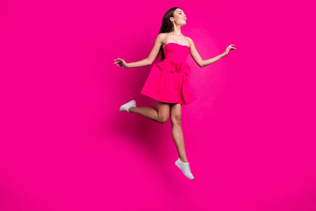 Вид ее в полный рост, она красивая, привлекательная, великолепная, увлекательная, беззаботная, веселая, длинноволосая, летящая, развлекающаяся, изолированная на ярком ярком сиянии яркого розового цвета фуксии.