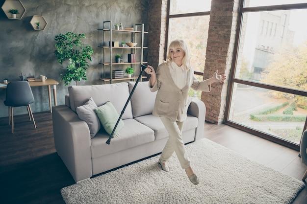 그녀의 전체 길이 몸 크기보기 그녀는 좋은 매력적인 건강하고 사랑스러운 쾌활한 회색 머리 할머니가 지팡이와 춤을 추며 산업 벽돌 로프트 모던 스타일 인테리어 하우스 아파트에서 재미