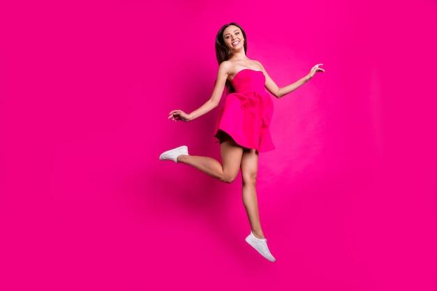 Вид ее в полный рост, она красивая привлекательная, привлекательная, веселая, длинноволосая девушка, летящая, развлекаясь, наслаждаясь свободным временем, изолированным на ярком ярком сиянии яркого розового цвета фуксии.