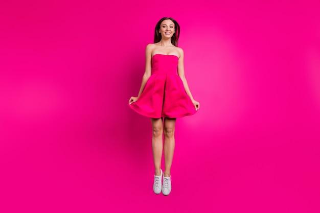Вид ее во весь рост, она красивая, привлекательная, очаровательная, увлекательная, веселая, длинноволосая девушка, прыгающая вверх, развлекаясь, изолирована на ярком ярком сияющем ярком розовом цветном фоне