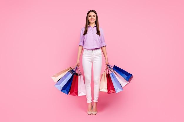 Вид в полный рост, она красивая, привлекательная, милая, модная, веселая, жизнерадостная девушка с покупками вещей, проводящая выходные, изолированные на розовом фоне пастельных тонов