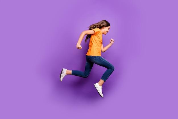 Вид ее в полный рост, она милая, привлекательная, симпатичная, веселая, веселая, с волнистыми волосами, прыгает, бегает быстро, изолированно на лиловом фиолетовом фиолетовом пастельном цвете