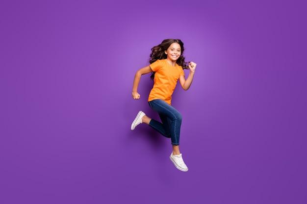 Вид ее в полный рост, она красивая, привлекательная, милая, рада, активная, веселая, веселая, с волнистыми волосами, прыгающая, бегущая весенний сезон, изолированная на сиреневом фиолетовом фиолетовом пастельном цвете