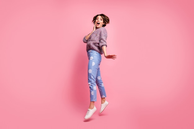 彼女の全身サイズのビュー彼女は素敵な魅力的な素敵な大喜び陽気な陽気な嬉しい興奮した恍惚とした茶色の髪の少女がピンクのパステルカラーの壁の上に孤立して楽しんでジャンプしています