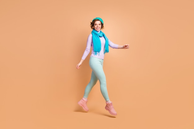 Вид ее в полный рост, она милая, привлекательная, симпатичная, симпатичная, веселая, веселая, прыгает, гуляет в современной мятно-лавандовой одежде, изолированной на бежевом пастельном цвете.