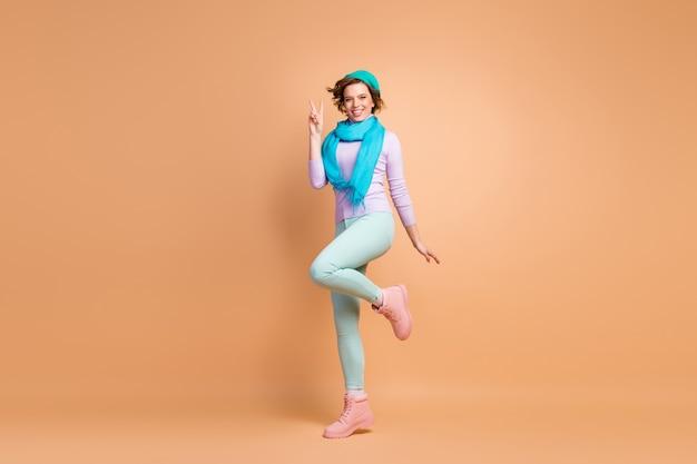 Вид ее в полный рост, она милая, привлекательная, симпатичная, довольно веселая, веселая девушка в мятно-лавандовой одежде, развлекающаяся, показывая знак v, изолированный на бежевом пастельном цвете
