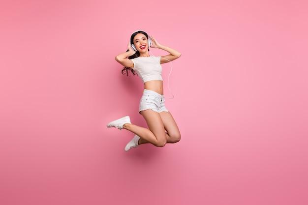 그녀의 전체 길이 몸 크기보기 그녀는 좋은 매력 사랑스럽고 쾌활한 쾌활한 물결 모양의 소녀 점프 재미 듣기 히트 노래 팝 영혼 핑크 파스텔 컬러 벽 위에 절연