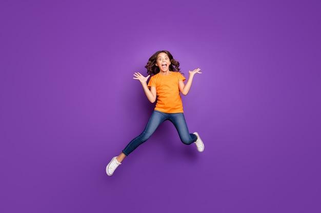 Вид ее в полный рост, она красивая, привлекательная, симпатичная, довольно сумасшедшая, обрадованная, веселая, веселая, с волнистыми волосами, прыгает, весело дурачится, изолирована на сиреневом фиолетовом фиолетовом пастельном фоне