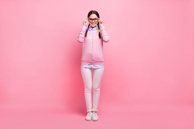 Вид ее в полный рост, она милая, привлекательная, симпатичная, симпатичная, умная, умная, веселая, веселая, веселая девушка-компьютерщик, носящая трогательные очки, изолированные на розовом фоне пастельных тонов.