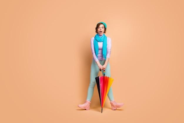 Вид в полный рост, она красивая, привлекательная, симпатичная, довольно забавная, веселая, веселая, веселая девушка с удовольствием дурачится, держа в руках зонтик, изолированный на бежевом пастельном цветном фоне