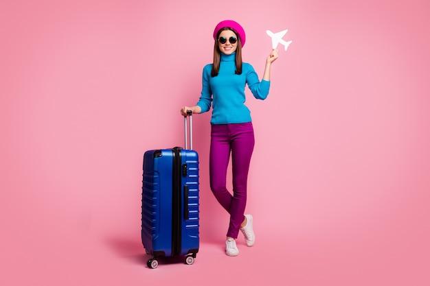 그녀의 전체 길이 몸 크기보기 그녀는 좋은 매력적인 사랑스러운 예쁜 슬림 맞는 쾌활한 명랑 소녀 손에 종이 비행기 기차역을 들고.