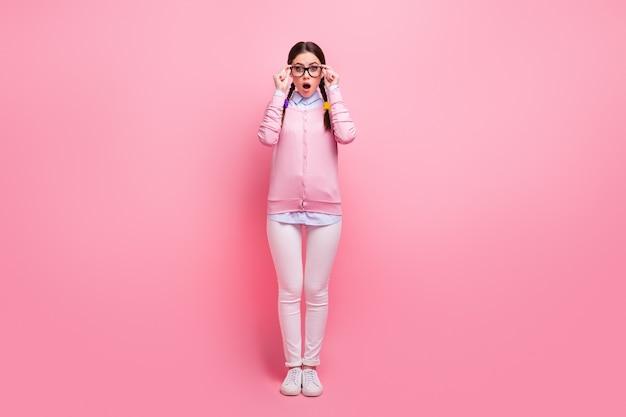 Вид ее в полный рост, она красивая, привлекательная, симпатичная, симпатичная, умная, умная, ошеломленная, ошеломленная девушка-компьютерщик, носящая трогательные характеристики, информационная реакция, изолированная на розовом пастельном цвете.