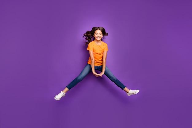 Вид ее в полный рост, она милая, привлекательная, симпатичная, веселая, веселая, с волнистыми волосами, прыгает, развлекаясь, изолирована на сиреневом фиолетовом фиолетовом пастельном фоне