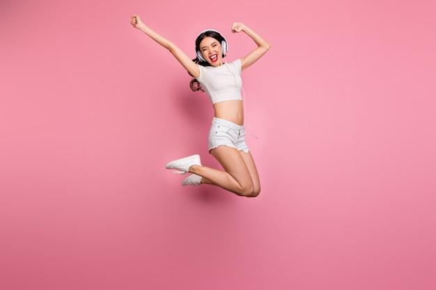 그녀의 전체 길이 몸 크기보기 그녀의 좋은 매력 사랑스러운 날씬한 맞는 슬림 얇은 쾌활한 쾌활한 물결 모양의 소녀 점프 재미 듣기 히트 핑크 파스텔 컬러 벽 위에 절연