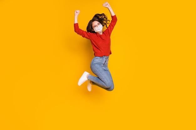 彼女の全身サイズのビュー彼女の素敵な魅力的な素敵なウェーブのかかった髪の少女は、明るい鮮やかな輝きの鮮やかな黄色の背景に分離された勝利の勝者を喜んでガーゼマスクを身に着けてジャンプします