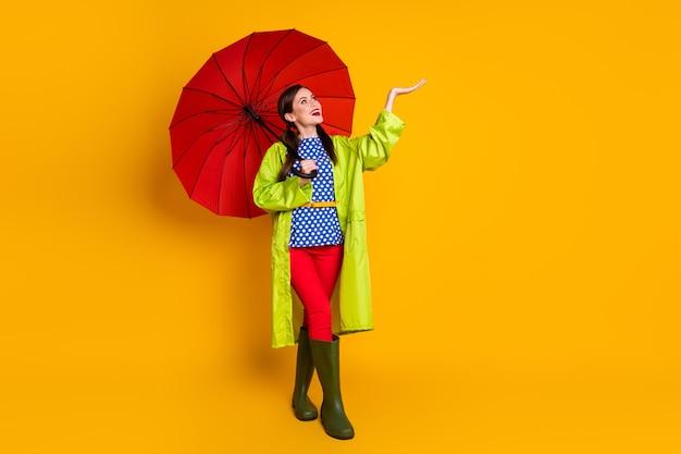 Вид ее в полный рост, она красивая, привлекательная, довольно веселая, веселая, радостная девушка в зеленом плаще, ловящая каплю дождя, изолирована, яркий яркий блеск, яркий желтый цвет фона
