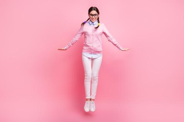 Вид ее в полный рост, она красивая, привлекательная, симпатичная, веселая, веселая, шатенка, прыгает, наслаждаясь свободой, развлекаясь, изолированный розовый пастельный цвет фона
