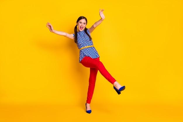 Полный размер тела вид на нее она красивая привлекательная довольно симпатичная классная стройная фигура веселая веселая фанк девушка притворяется падающей весело изолированные яркий яркий блеск яркий желтый цвет фона