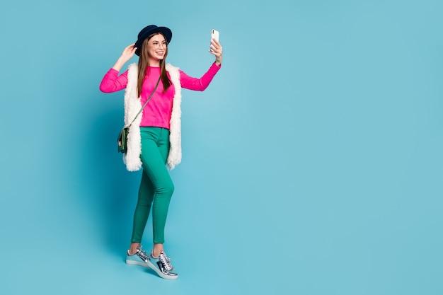 Вид ее в полный рост, она красивая, привлекательная, симпатичная, модная, веселая, веселая, девушка, делающая селфи, изолирована на ярко-ярком сиянии яркой зеленой голубой бирюзовой стене