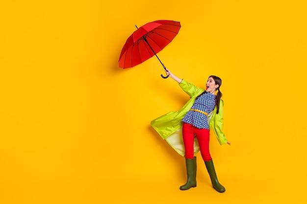 Вид ее в полный рост, она красивая, привлекательная, модная, веселая, веселая, забавная девичья девушка в зеленом пальто, борющаяся с ветром, изолирована, яркий яркий блеск, яркий желтый цвет фона