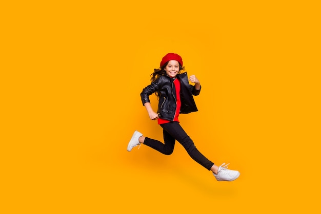그녀의 전체 길이 몸 크기보기 그녀의 좋은 매력적인 트렌디 한 쾌활한 펑키 장발 소녀 점프 달리기 빠른 서둘러 재미 밝고 선명한 광택 생생한 노란색 벽 위에 절연