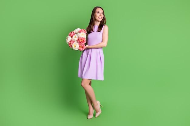 Вид ее в полный рост, она красивая привлекательная очаровательная стройная стройная стройная веселая мечтательная девушка, держащая в руках букет свежих цветов, изолированный зеленый цвет фона
