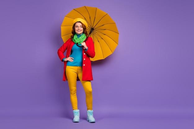 Вид в полный рост, она красивая, привлекательная, симпатичная, довольно модная, веселая, мечтательная, с волнистыми волосами, девушка с зонтиком, позирующая изолированно на фиолетово-сиреневом пурпурном фоне пастельных тонов.