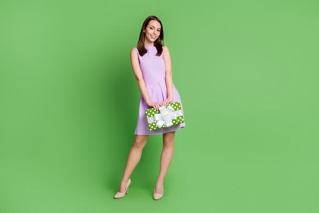 Полный размер тела вид ее она красивая привлекательная довольно элегантная веселая веселая девушка держит в руках пунктирную подарочную коробку поздравить праздничный случай изолированный зеленый цвет фона