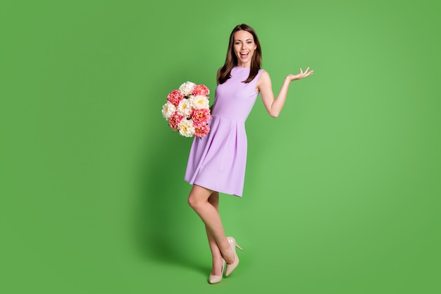 Вид ее в полный рост, она красивая, привлекательная, симпатичная, очаровательная, веселая, веселая, девушка, держащая в руках букет свежих цветов, развлекается на изолированном зеленом цветном фоне