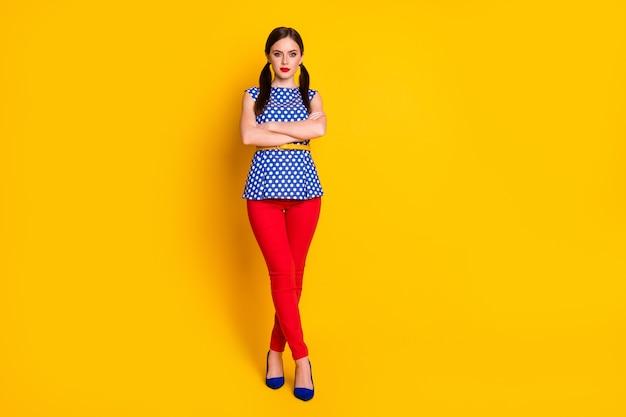 彼女の全身サイズのビュー彼女の見栄えの良い魅力的なかなり素敵な魅力的なコンテンツの女の子腕を組んで孤立した明るい鮮やかな輝き鮮やかな黄色の背景