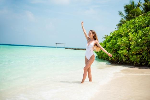 Вид ее в полный рост, она красивая, привлекательная, спортивная, стройная, стройная, стройная девушка, собирающаяся наслаждаться солнечным жарким днем, теплым лазурным морем, чистым, чистым песком, пляжем бали, гавайи, расслабиться