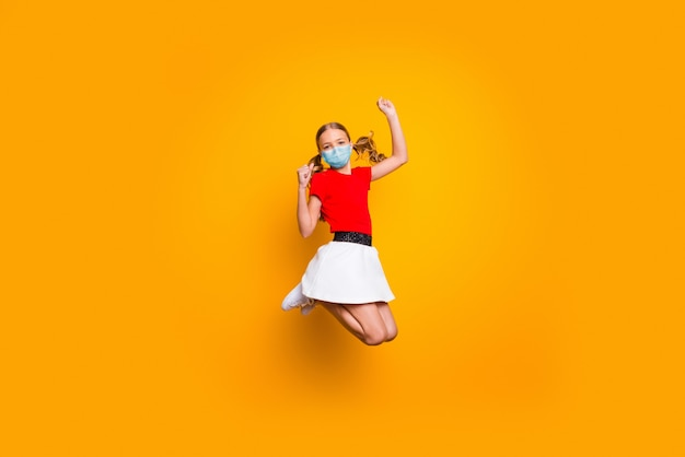 安全ガーゼマスクを身に着けてジャンプする彼女のかわいい女の子の全身サイズのビュー健康的な生活を停止するmerscov汚染分離された明るい黄色の背景