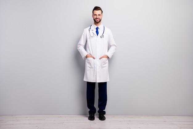 그는 밝은 흰색 회색 파스텔 색상에 고립 된 주머니에 손을 잡고 그의 좋은 매력적인 쾌활한 명랑 전문 의사 우수한 전문가 응급 처치 서비스의 전체 길이 몸 크기보기