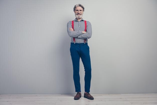회색 파스텔 컬러 배경 벽 위에 절연 품위있는 표정을 입고 팔짱을 끼고 서있는 그의 좋은 매력적인 잘 차려 입은 유행 쾌활한 쾌활한 남자의 전체 길이 몸 크기보기