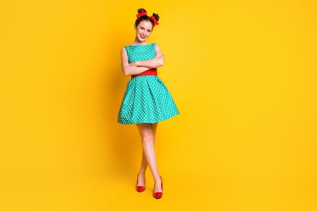Вид в полный рост прекрасной жизнерадостной девушки в чирковом платье, сложенной баранами, изолированными на ярко-желтом цветном фоне