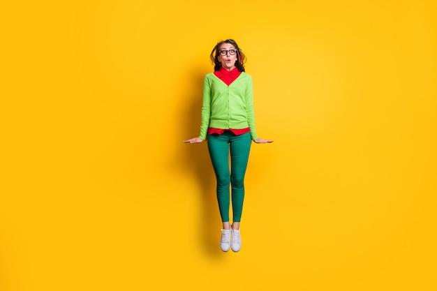 Вид в полный рост прекрасной застенчивой фанки удивленной веселой девушки, прыгающей, позирующей надутыми губами, изолировал ярко-желтый цвет фона