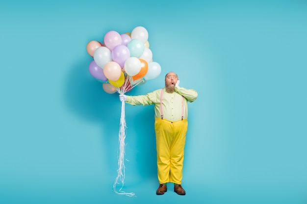 Вид в полный рост зрелого парня, держащего в руках возбужденные воздушные шары
