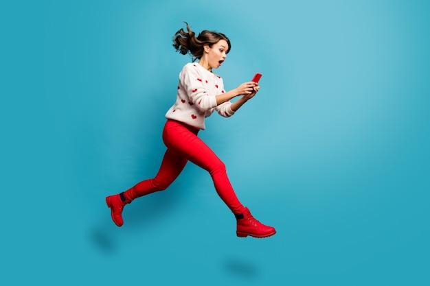 フォローサブスクライブ急いで急いで5gを使用してジャンプする素敵な魅力的な陽気な驚いた感動の女の子の全身サイズのビュー