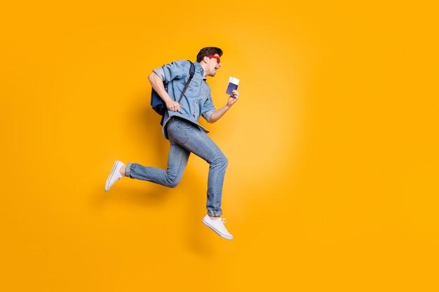 Красивый привлекательный веселый веселый парень в полный рост прыгает в сезон отдыха во время бега, держа в руке билеты, изолированные над яркой яркой стеной яркого желтого цвета