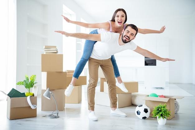 Вид в полный рост красивой привлекательной веселой пары, держащей свинью, летящей, как покупка самолета, аренда недвижимости, кредит, безопасность, инвестиционное страхование, поездка в светлый белый интерьер дома