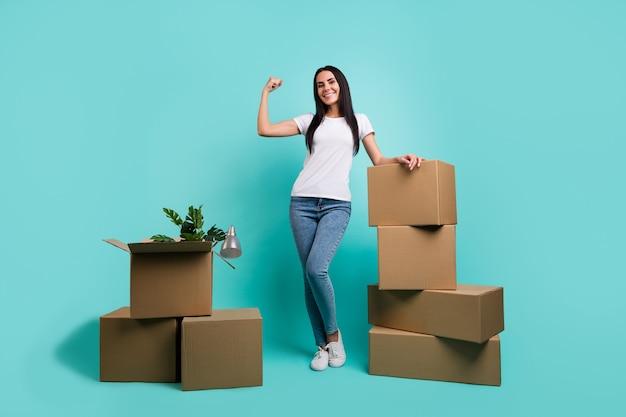 Вид в полный рост красивой привлекательной жизнерадостной девушки, показывающей мышцы, упаковывающие вещи, стопку коробок